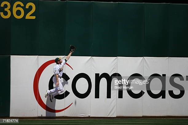 Bobby Kielty of the Oakland Athletics makes a leaping attempt in front of a Comcast ad on the wall during the game against the Texas Rangers at the...