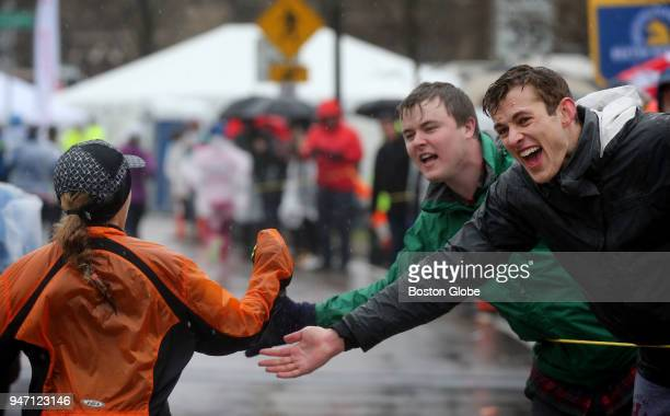 Bobby Looney center and Justin Mundt right offer encouragement to a runner as they crest Heartbreak Hill during the Boston Marathon in Newton Mass...