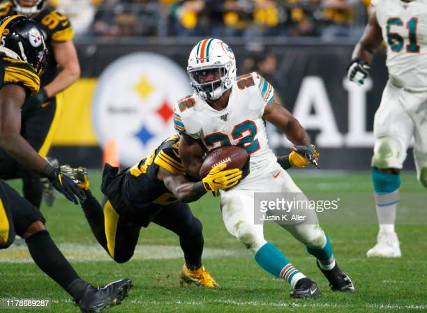 Bobby McCain of the Miami Dolphins strips Mark Walton of the Miami Dolphins in the second half on October 28 2019 at Heinz Field in Pittsburgh...