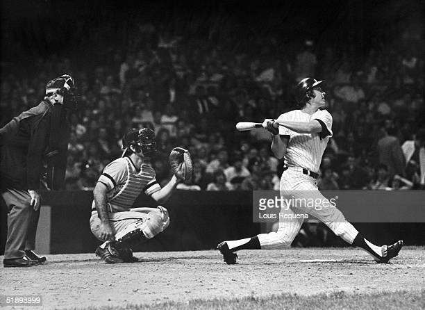 Bobby Murcer of the New York Yankees follows through on his swing as catcher Andy Etchebarren of the Baltimore Orioles looks on during a game at...