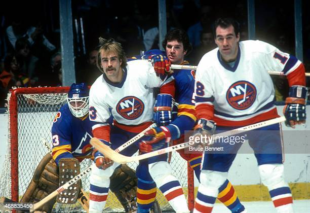 Bobby Nystrom and Ed Westfall of the New York Islanders battle with Barry Beck of the Colorado Rockies for position in front of goalie Doug Favell of...
