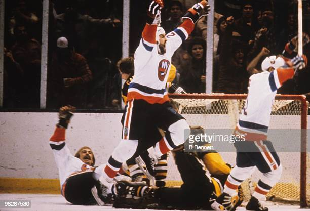 Bobby Nystrom , John Tonelli and Butch Goring of the New York Islanders celebrate Nystrom's overtime game-winning goal in Game 5 of their divisional...