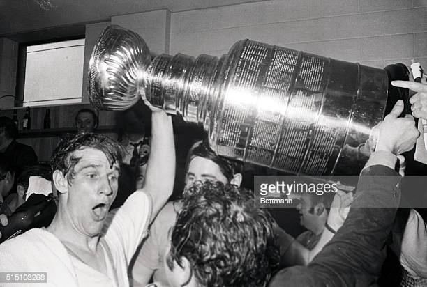 Bobby Orr helps raise the Stanley Cup in the locker room following the Bruins' Game 4 finals victory over the St Louis Blues Orr scored the...