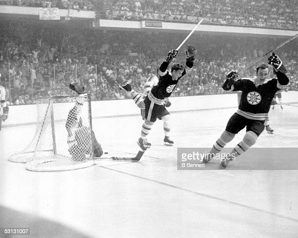 Bobby Orr of the Boston Bruins flies through the air after sliding the puck past goalie Glenn Hall and tripped by Noel Picard of the St. Louis Blues...