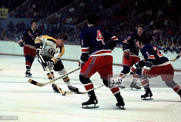 Bobby Orr of the Boston Bruins skates with the puck against the New York Rangers defense during a game circa 1970's at the Boston Garden in Boston...