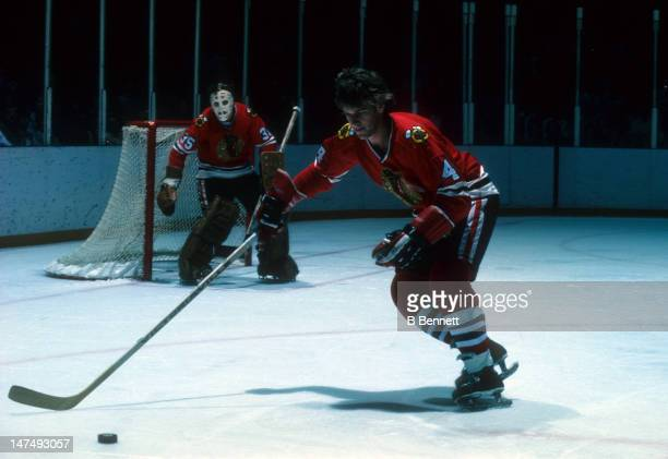 Bobby Orr of the Chicago Blackhawks skates with the puck as goalie Tony Esposito looks on during their NHL game circa 1979