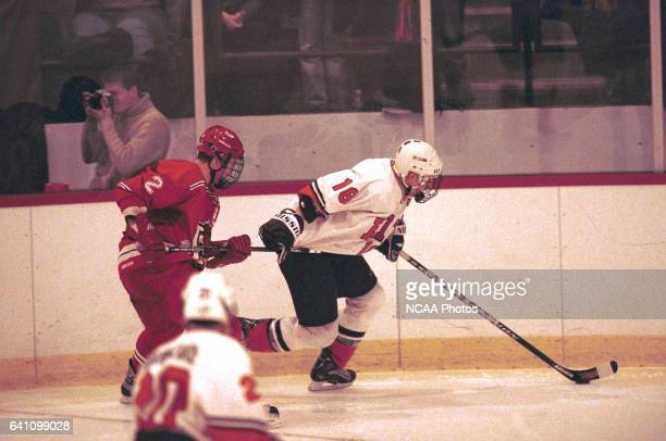 Bobby Owen of Plattsburg State University hooks Derek Hahn of Rochester Institute of Technology during the 2001 NCAA Men's Ice Hockey Championship...