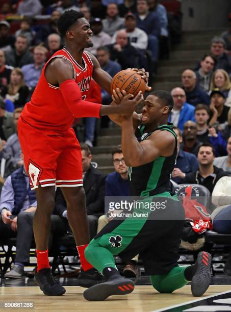 Bobby Portis of the Chicago Bulls and Guerschon Yabusele of the Boston Celtics battle for the ball at the United Center on December 11 2017 in...