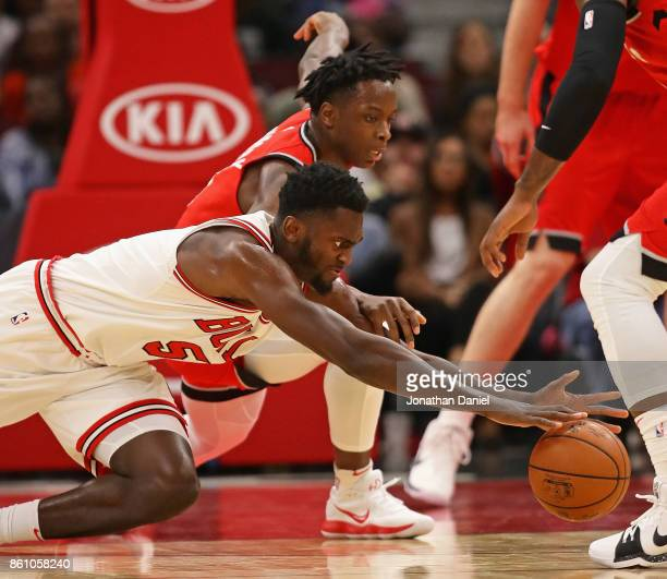 Bobby Portis of the Chicago Bulls and OG Anunoby of the Toronto Raptors dives for a lose ball during a preseason game at the United Center on October...