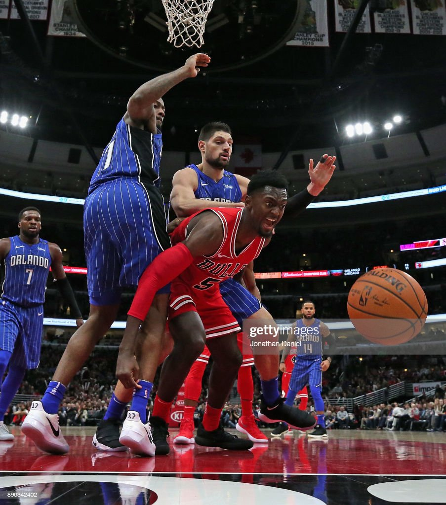 Bobby Portis #5 of the Chicago Bulls looses control of the ball under pressure from Jonathon Simmons #17 and Nikola Vucevic #9 of the Orlando Magic at the United Center on December 20, 2017 in Chicago, Illinois. The Bulls defeated the Magic 112-94.