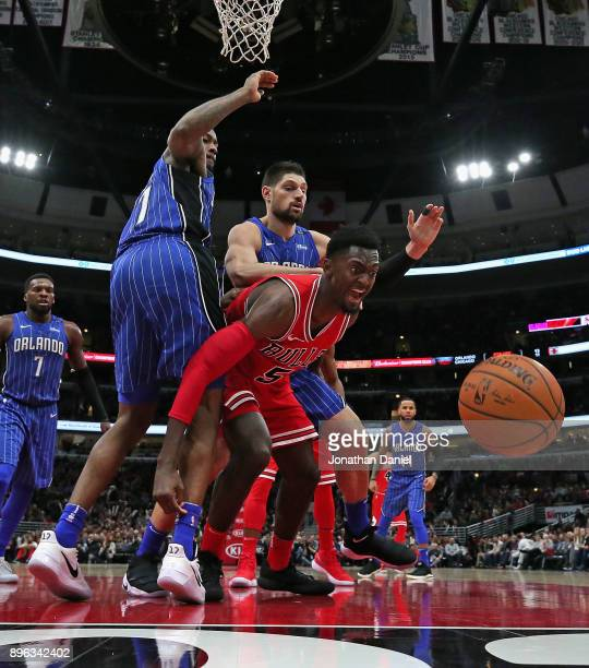Bobby Portis of the Chicago Bulls looses control of the ball under pressure from Jonathon Simmons and Nikola Vucevic of the Orlando Magic at the...