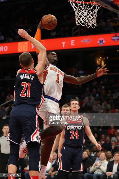 Bobby Portis of the New York Knicks dunks on Moritz Wagner of the Washington Wizards during the first half at Capital One Arena on March 10 2020 in...