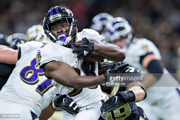 Bobby Rainey of the Baltimore Ravens is tackled by Adam Bighill of the New Orleans Saints during a preseason game at MercedesBenz Superdome on August...