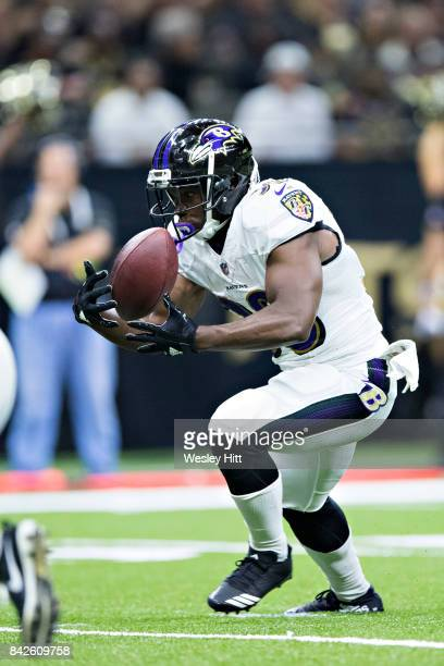 Bobby Rainey of the Baltimore Ravens mishandles the handoff during a preseason game against the New Orleans Saints at MercedesBenz Superdome on...