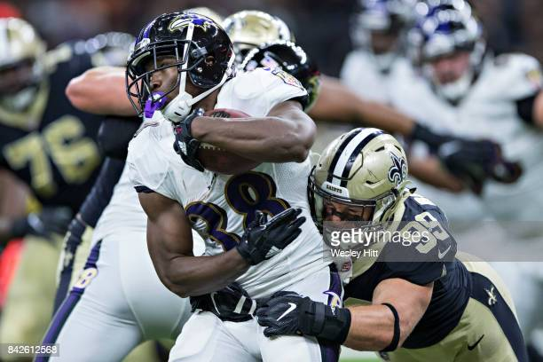 Bobby Rainey of the Baltimore Ravens runs the ball and is tackled by Adam Bighill of the New Orleans Saints during a preseason game at MercedesBenz...