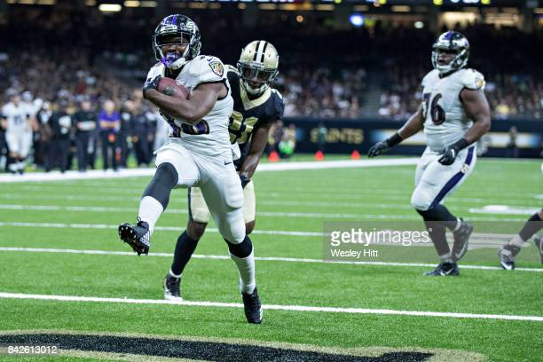 Bobby Rainey of the Baltimore Ravens rushes for a touchdown past De'Vante Harris of the New Orleans Saints during a preseason game at MercedesBenz...