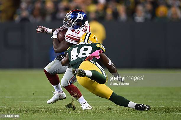 Bobby Rainey of the New York Giants avoids a tackle by Joe Thomas of the Green Bay Packers during a game at Lambeau Field on October 9 2016 in Green...