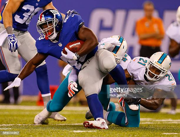 Bobby Rainey of the New York Giants is tackled by Spencer Paysinger and Jordan Lucas of the Miami Dolphins during the first half of an NFL preseason...