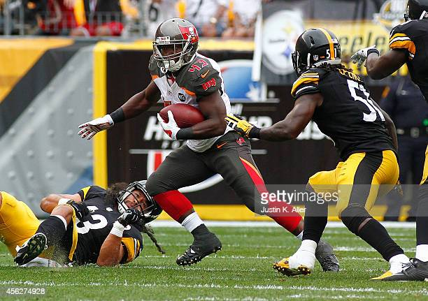 Bobby Rainey of the Tampa Bay Buccaneers carries the ball in front of Sean Spence of the Pittsburgh Steelers during the second quarter at Heinz Field...