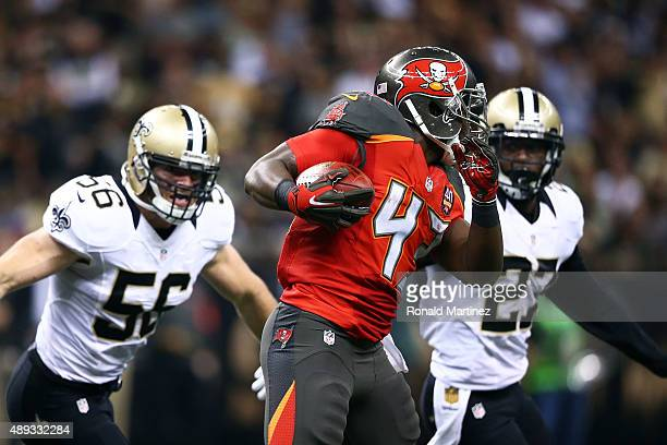 Bobby Rainey of the Tampa Bay Buccaneers is pursued by Michael Mauti and Damian Swann of the New Orleans Saints during the third quarter of a game at...