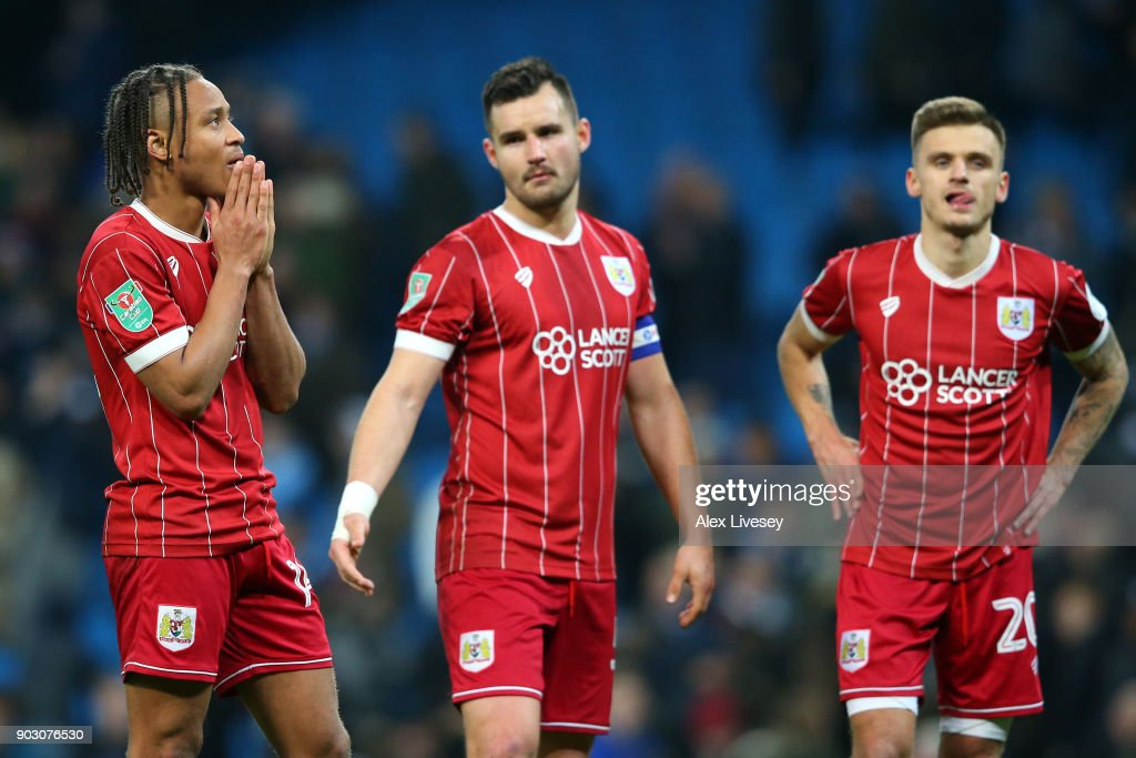 Bobby Reid, Bailey Wright and Jamie Paterson of Bristol City look dejected in defeat after the Carabao Cup Semi-Final First Leg match between Manchester City and Bristol City at Etihad Stadium on January 9, 2018 in Manchester, England.