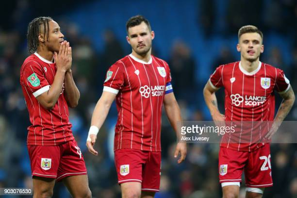 Bobby Reid Bailey Wright and Jamie Paterson of Bristol City look dejected in defeat after the Carabao Cup SemiFinal First Leg match between...