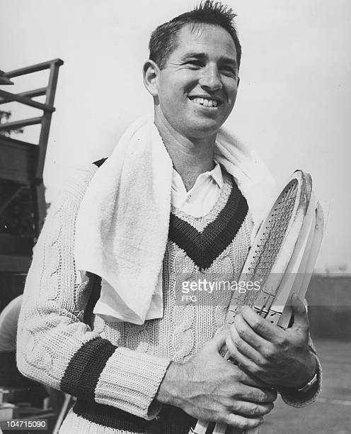 Bobby Riggs American tennis player smiles with a towel around his neck while holding a number of wooden tennis rackets circa 1940