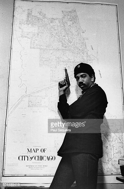 Bobby Rush poses with a gun in front of a map of Chicago at the Black Panthers Party office Chicago Illinois 1969