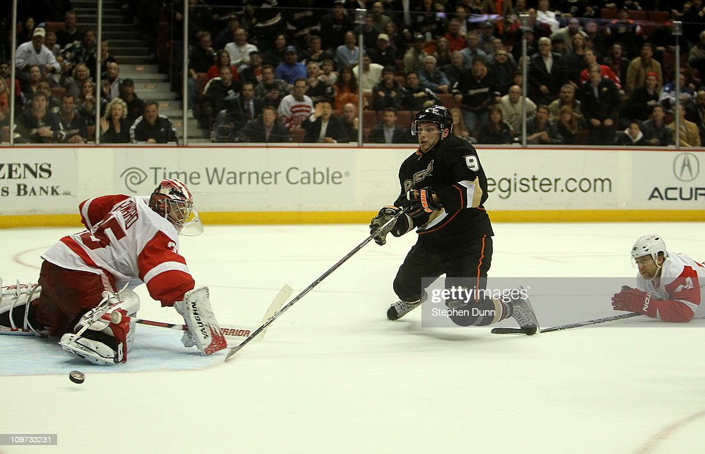 Bobby Ryan #9 of the Anaheim Ducks is tripped from behind by Ruslan Salei #24 of the Detroit Red Wings as the puck goes by Red Wings goalie Jimmy Howard #35 on March 2, 2011 at the Honda Center in Anaheim, California. Ryan was awarded a penalty shot on the play, which he converted for the winning goal as the Ducks won 2-1 in overtime.