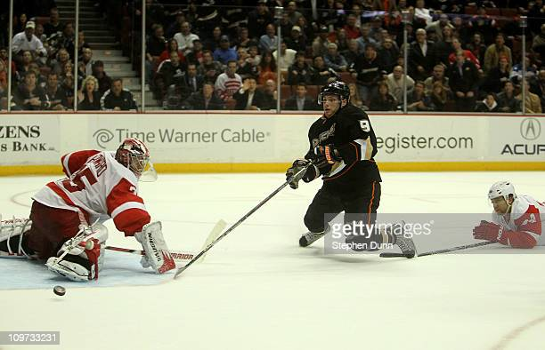Bobby Ryan of the Anaheim Ducks is tripped from behind by Ruslan Salei of the Detroit Red Wings as the puck goes by Red Wings goalie Jimmy Howard on...