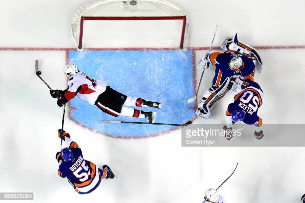 Bobby Ryan of the Ottawa Senators attempts a shot on goal as he falls to the ice as Thomas Greiss of the New York Islanders tends to net and Johnny...
