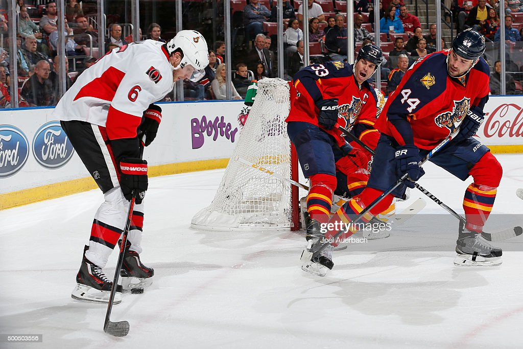 Bobby Ryan #6 of the Ottawa Senators attempts to center the puck as Erik Gudbranson #44 and Willie Mitchell #33 of the Florida Panthers help defend the net at the BB&T Center on December 8, 2015 in Sunrise, Florida. The Senators defeated the anthers 4-2.