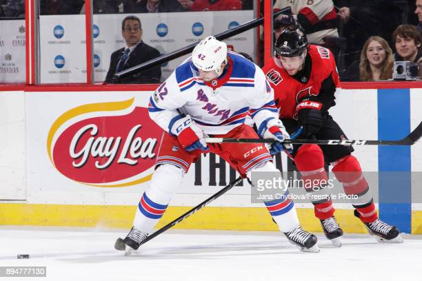 Bobby Ryan of the Ottawa Senators battles for the loose puck against Brendan Smith of the New York Rangers at Canadian Tire Centre on December 13...