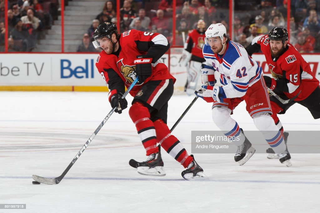 Bobby Ryan #9 of the Ottawa Senators skates with the puck against Brendan Smith #42 of the New York Rangers as Zack Smith #15 pursues the play at Canadian Tire Centre on December 13, 2017 in Ottawa, Ontario, Canada.