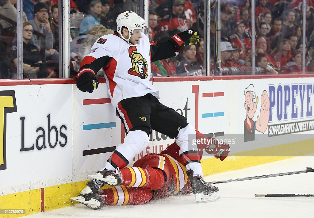 Bobby Ryan #65 of the Ottawa Senators tries to stay upright after colliding with Dougie Hamilton #27 of the Calgary Flames during their NHL game at the Scotiabank Saddledome on February 27, 2016 in Calgary, Alberta, Canada.