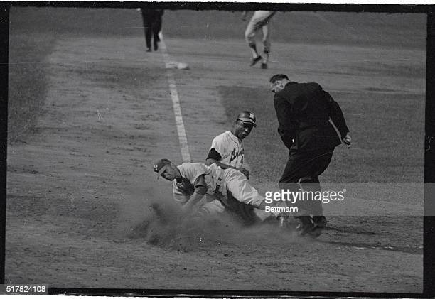 Bobby Shantz Philadelphia Phillies pitcher is knocked off his feet covering the home plate here as Milwaukee Braves right fielder Hank Aaron scores...