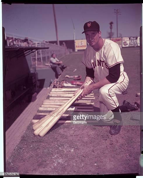 Bobby Thomson, Giants baseball player, smiling as he holds baseball bats over his shoulder.