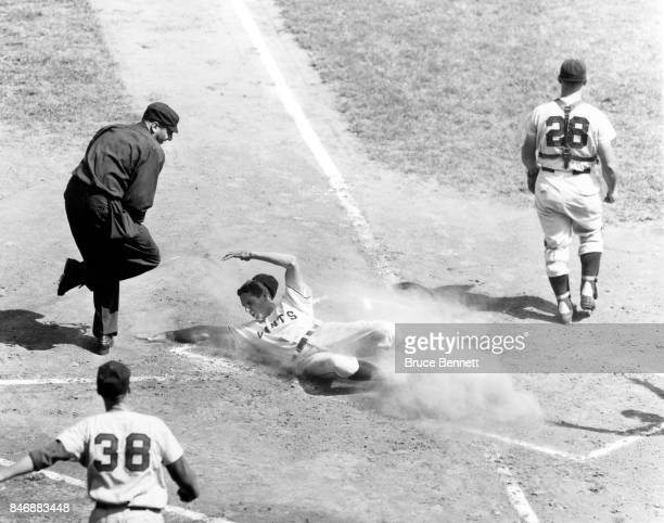 Bobby Thomson of the New York Giants slides safely into home as catcher Andy Seminick and pitcher Bud Podbielan of the Cincinnati Redlegs wait for...