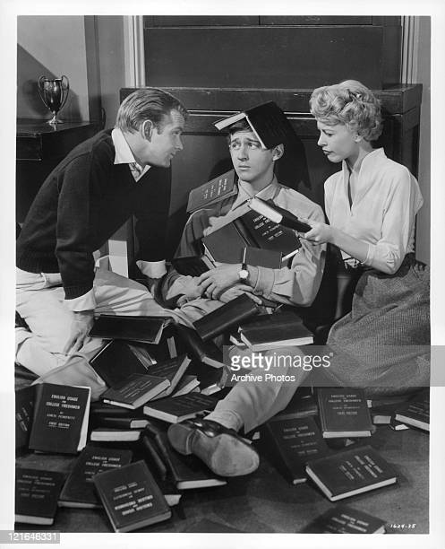 Bobby Van And Barbara Ruick discuss used books in a library in a scene from the film 'Affairs Of Dobie Gillis' 1953