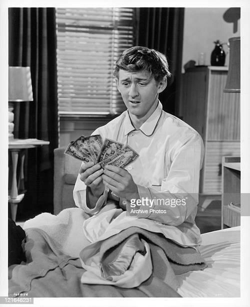 Bobby Van counts money in bed in a scene from the film 'Affairs Of Dobie Gillis' 1953