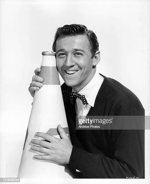 Bobby Van holds blow horn in a scene from the film 'Affairs Of Dobie Gillis' 1953