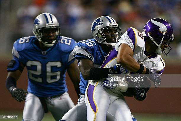 Bobby Wade of the Minnesota Vikings tries to break free from Fernando Bryant and Kenoy Kennedy of the Detroit Lions during the fourth quarter at Ford...