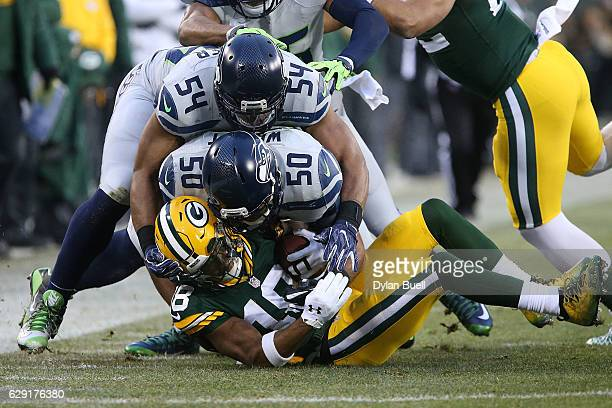 Bobby Wagner and KJ Wright of the Seattle Seahawks tackle Randall Cobb of the Green Bay Packers during the first half of a game at Lambeau Field on...