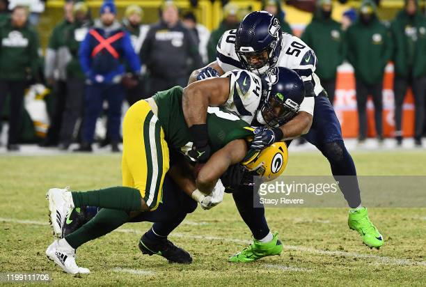 Bobby Wagner of the Seattle Seahawks tackles Aaron Jones of the Green Bay Packers during the first half in the NFC Divisional Playoff game at Lambeau...