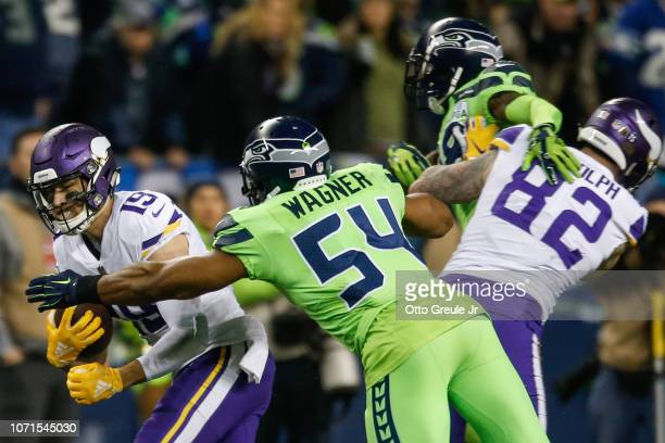 Bobby Wagner of the Seattle Seahawks tackles Adam Thielen of the Minnesota Vikings in the third quarter at CenturyLink Field on December 10 2018 in...