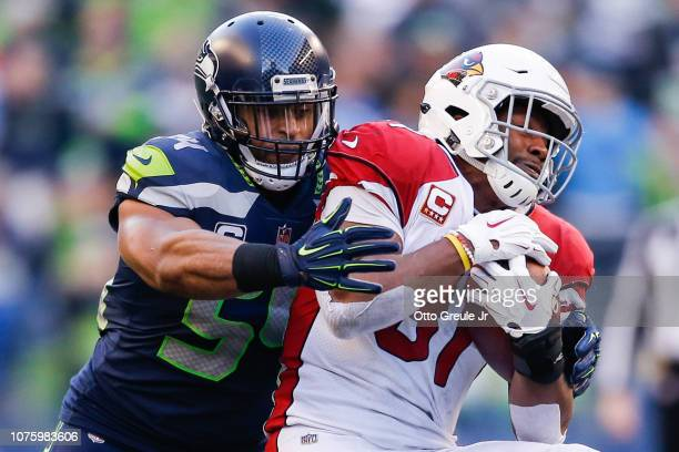 Bobby Wagner of the Seattle Seahawks tackles David Johnson of the Arizona Cardinals in the third quarter at CenturyLink Field on December 30 2018 in...
