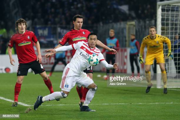 Bobby Wood of Hamburg is challenged by Nicolas Hoefler of Freiburg during the Bundesliga match between SportClub Freiburg and Hamburger SV at...