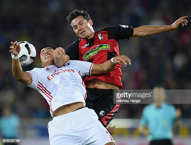 Bobby Wood of Hamburg jumps for a header with Nicolas Hoefler of Freiburg during the Bundesliga match between SC Freiburg and Hamburger SV at...