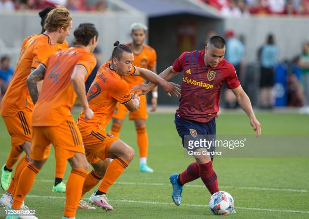 Bobby Wood of Real Salt Lake tries to get a shot off while being held by Sam Junqua of the Houston Dynamo during their game on June 26, 2021 at Rio...