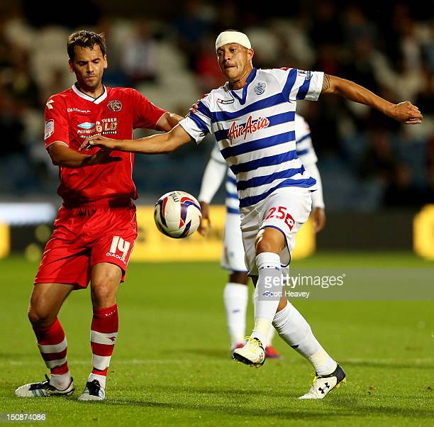 Bobby Zamora of QPR in action with Ben Purkiss of Walsall during the Capital One Cup Second Round match between Queens Park Rangers and Walsall at...
